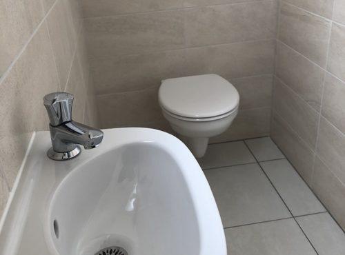 Carrelage beige pour ces toilettes suspendues.