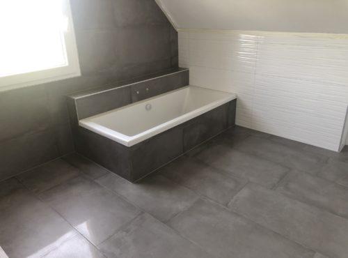 Salle de bain avec baignoire habillage carrelage effet béton