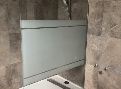 Douche avec carrelage effet marbré et bac à douche blanc